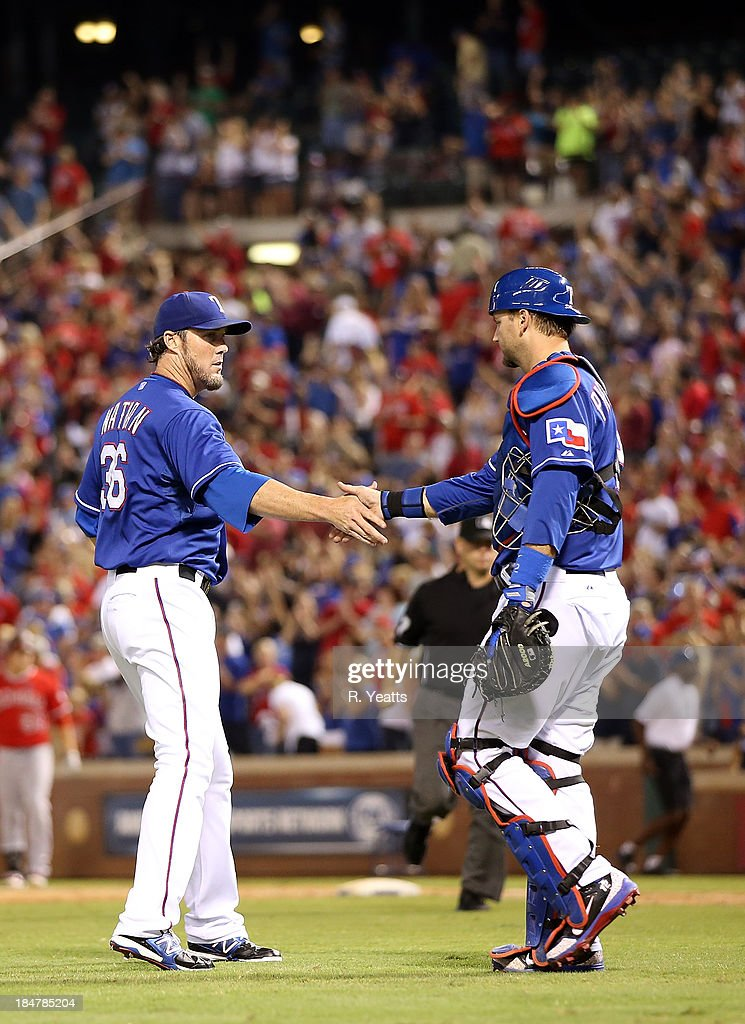 Joe Nathan #36 of the Texas Rangers is congratulated by A.J. Pierzynski #12 foreclosing out the game for the win against the Los Angeles Angels of Anaheim at Rangers Ballpark on September 27, 2013 in Arlington, Texas.