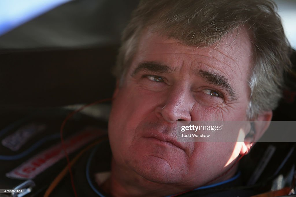 Joe Nemechek driver of the Land Castle Title Toyota sits in his car during qualifying for the NASCAR Sprint Cup Series Auto Club 400 at Auto Club...