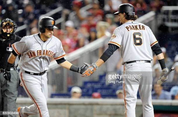 Joe Panik of the San Francisco Giants celebrates with Jarrett Parker after hitting a home run in the first inning against the Washington Nationals at...