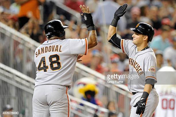 Joe Panik of the San Francisco Giants celebrates with Pablo Sandoval after hitting a threerun home run in the fourth inning against the Washington...