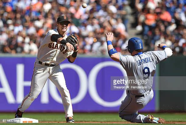 Joe Panik of the San Francisco Giants completes the doubleplay throwing over the top of Yasmani Grandal of the Los Angeles Dodgers in the top of the...