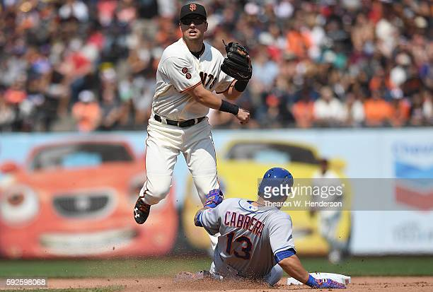 Joe Panik of the San Francisco Giants gets his throw off to complete the doubleplay over the top of Asdrubal Cabrera of the New York Mets in the top...