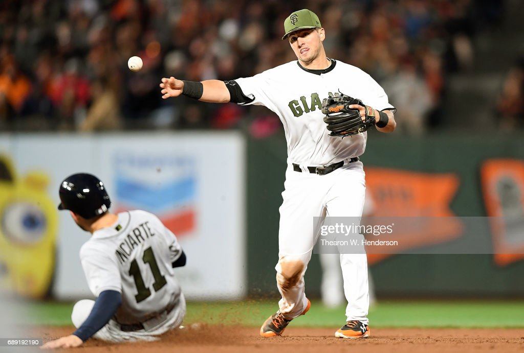 Joe Panik #12 of the San Francisco Giants gets his throw off to complete the double-play over the top of Ender Inciarte #11 of the Atlanta Braves in the top of the six inning at AT&T Park on May 27, 2017 in San Francisco, California.