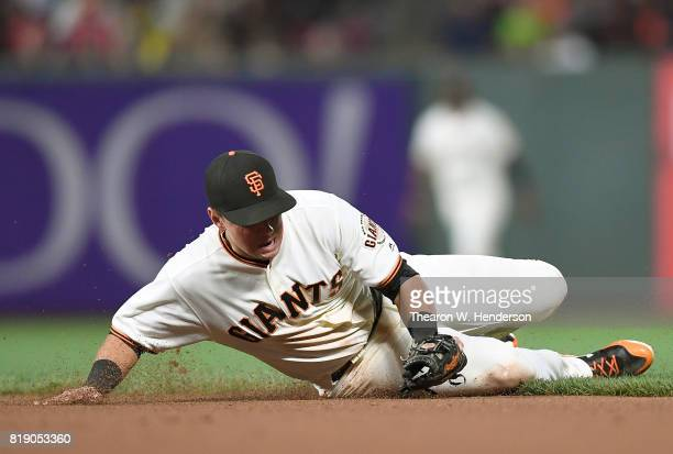 Joe Panik of the San Francisco Giants goes into a slide on one knee to field a ground ball taking a hit away from Michael Brantley of the Cleveland...