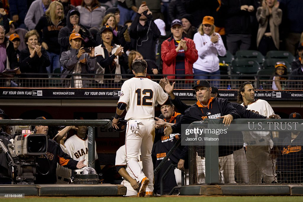 Joe Panik #12 of the San Francisco Giants is congratulated by manager Bruce Bochy #15 after scoring a run against the Oakland Athletics during the sixth inning at AT&T Park on July 9, 2014 in San Francisco, California. The Giants defeated the Athletics 5-2.