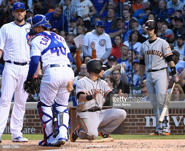 Joe Panik of the San Francisco Giants is safe at home ahead of the throw to catcher Willson Contreras of the Chicago Cubs during the third inning on...