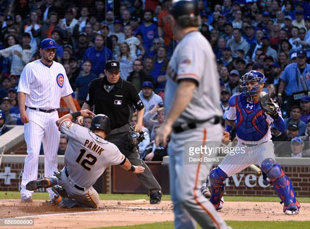 Joe Panik of the San Francisco Giants is safe at home as Willson Contreras of the Chicago Cubs gets a late throw during the third inning on May 20...