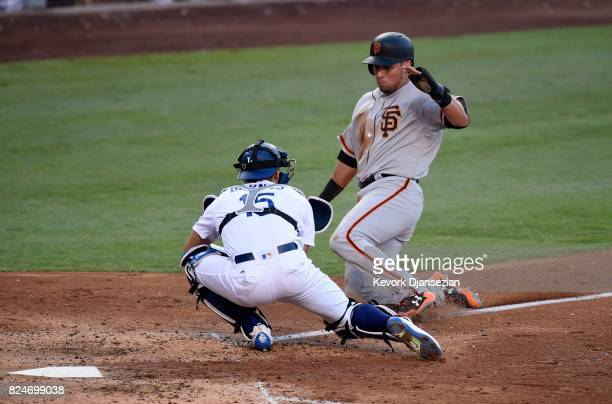 Joe Panik of the San Francisco Giants is tagged out at home plate by catcher Austin Barnes of the Los Angeles Dodgers during the seventh inning at...