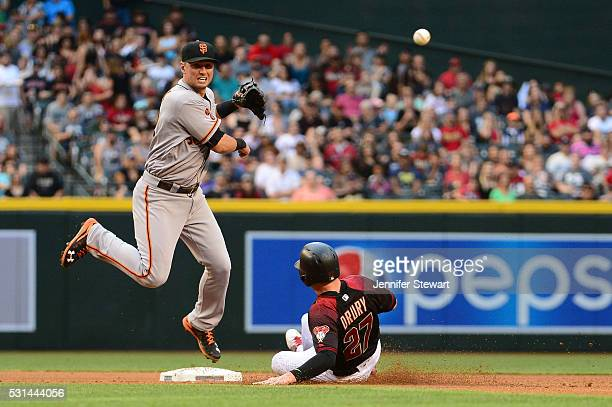 Joe Panik of the San Francisco Giants makes the force out at second base on Brandon Drury of the Arizona Diamondbacks in the fourth inning at Chase...