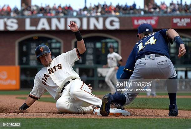 Joe Panik of the San Francisco Giants steals third base as the throw gets by Hernan Perez of the Milwaukee Brewers in the bottom of the fourth inning...