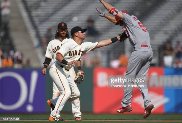 Joe Panik of the San Francisco Giants tags out Stephen Piscotty of the St Louis Cardinals in the top of the tenth inning at ATT Park on September 2...