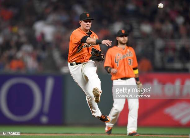 Joe Panik of the San Francisco Giants throws off balance to first base throwing out Stephen Piscotty of the St Louis Cardinals in the top of the...