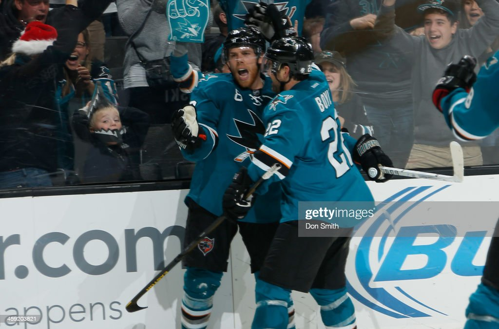 Joe Pavelski #8 and Dan Boyle #22 of the San Jose Sharks celebrate after a goal against the Colorado Avalanche during an NHL game on December 23, 2013 at SAP Center in San Jose, California.