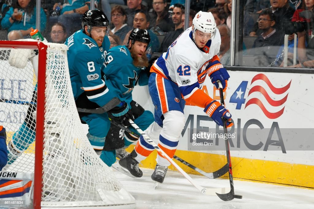 Joe Pavelski #8 and Joe Thornton #19 of the San Jose Sharks along with Scott Mayfield #42 of the New York Islanders battle for the puck at SAP Center on October 14, 2017 in San Jose, California.
