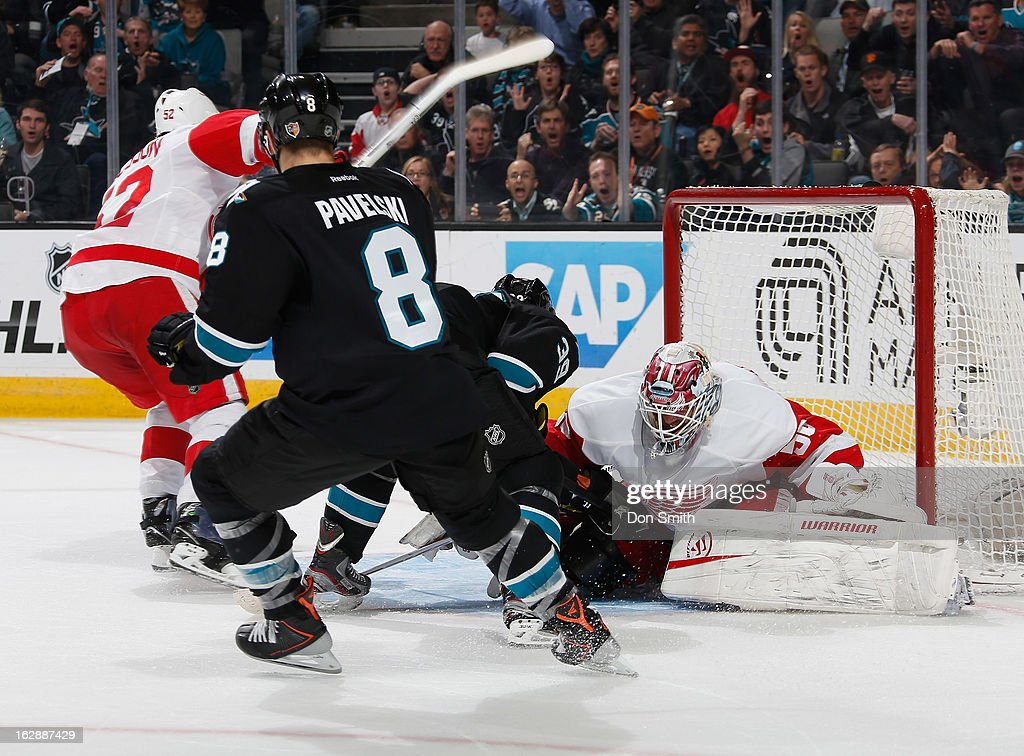 Joe Pavelski #8 and Logan Couture #39 of the San Jose Sharks crash the net against Jonas Gustavsson #50 and Jonathan Ericsson #52 of the Detroit Red Wings during an NHL game on February 28, 2013 at HP Pavilion in San Jose, California.