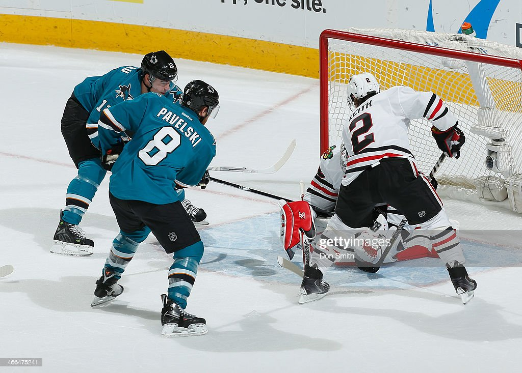 Joe Pavelski #12 and Patrick Marleau #12 of the San Jose Sharks try to score against Corey Crawford #50 and Duncan Keith #2 of the Chicago Blackhawks during an NHL game on February 1, 2014 at SAP Center in San Jose, California.