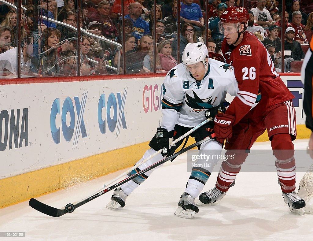 Joe Pavelski #8 of the San Jose Sharks and Michael Stone #26 of the Arizona Coyotes battle for the puck behind the net during the third period at Gila River Arena on February 13, 2015 in Glendale, Arizona.
