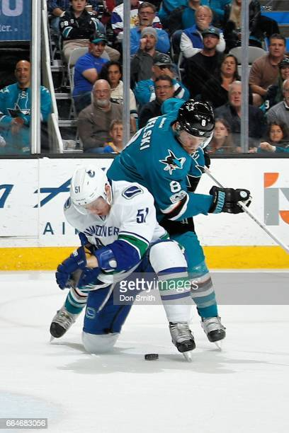 Joe Pavelski of the San Jose Sharks and Troy Stecher of the Vancouver Canucks battle for the puck at SAP Center at San Jose on April 4 2017 in San...