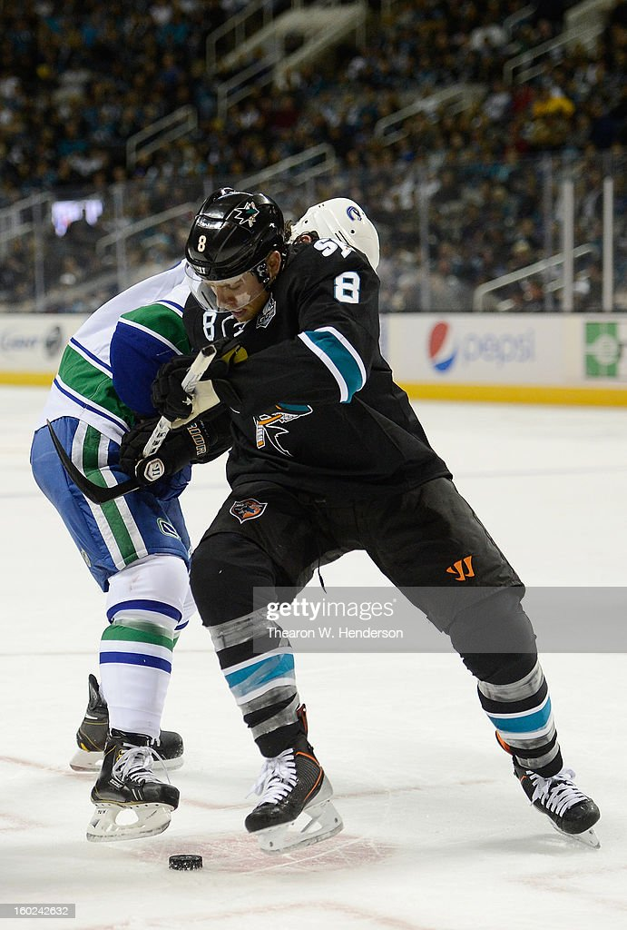 Joe Pavelski #8 of the San Jose Sharks battles for control of the puck with Zack Kassian #9 of the Vancouver Canucks at HP Pavilion on January 27, 2013 in San Jose, California.