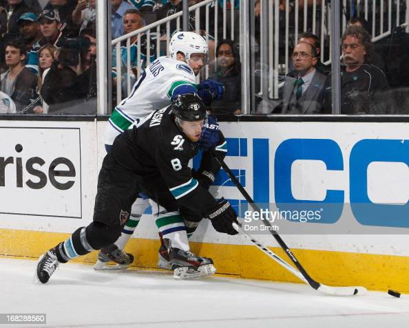 Joe Pavelski of the San Jose Sharks fights for the puck against Dan Hamhuis of the Vancouver Canucks in Game Four of the Western Conference...