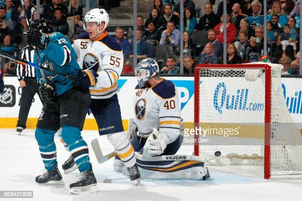 Joe Pavelski of the San Jose Sharks gets the puck by Rasmus Ristolainen and Robin Lehner of the Buffalo Sabres to score a second period goal during a...