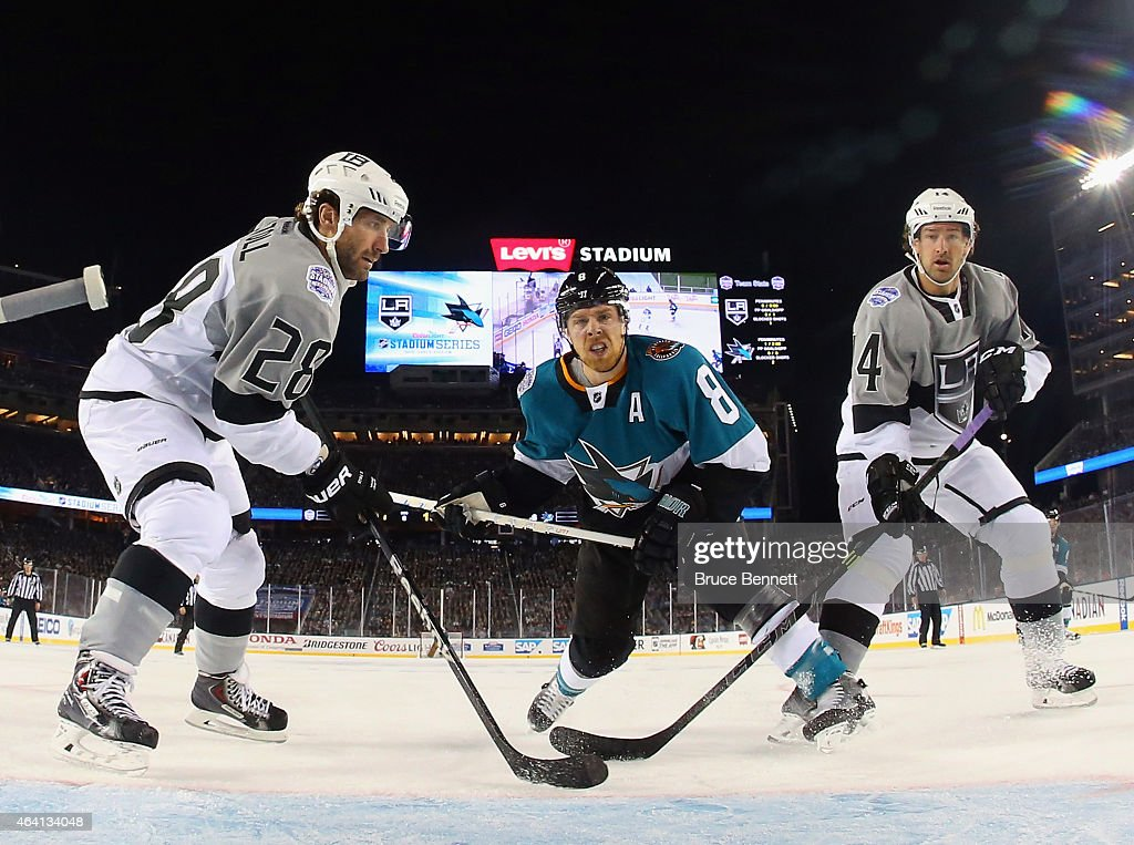 Joe Pavelski #8 of the San Jose Sharks goes up against Jarret Stoll #28 and Justin Williams #14 of the Los Angeles Kings during the 2015 Coors Light NHL Stadium Series game at Levi's Stadium on February 21, 2015 in Santa Clara, California. The Kings defeated the Sharks 2-1.