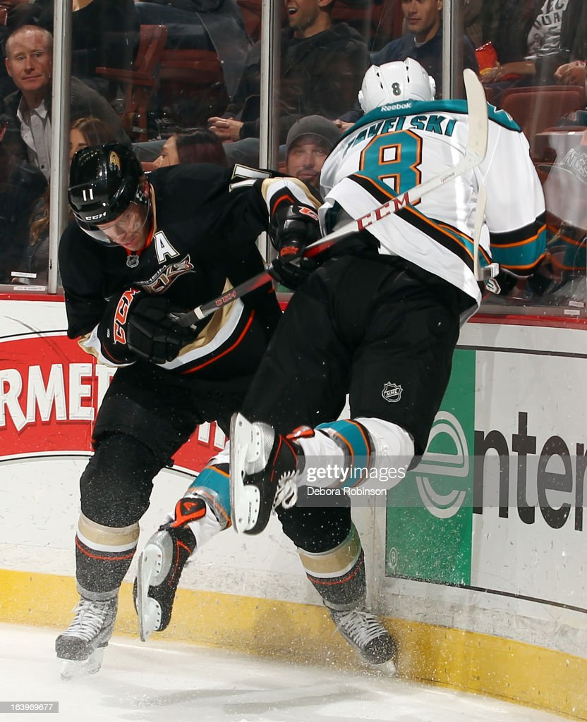 Joe Pavelski #8 of the San Jose Sharks is checked into the boards by Saku Koivu #11 of the Anaheim Ducks on March 18, 2013 at Honda Center in Anaheim, California.