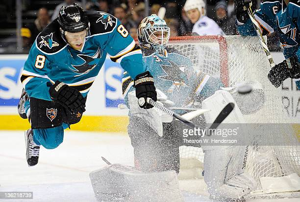 Joe Pavelski of the San Jose Sharks is tripped up going after the puck deflected away from the net by goaltender Antti Niemi against the Vancouver...