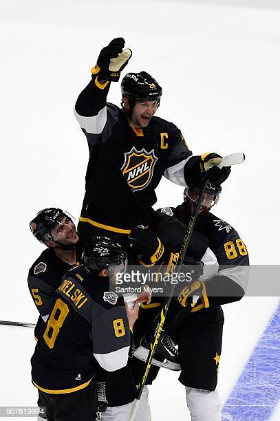 Joe Pavelski of the San Jose Sharks Mark Giordano of the Calgary Flames and Brent Burns of the San Jose Sharks hoist John Scott of the Arizona...