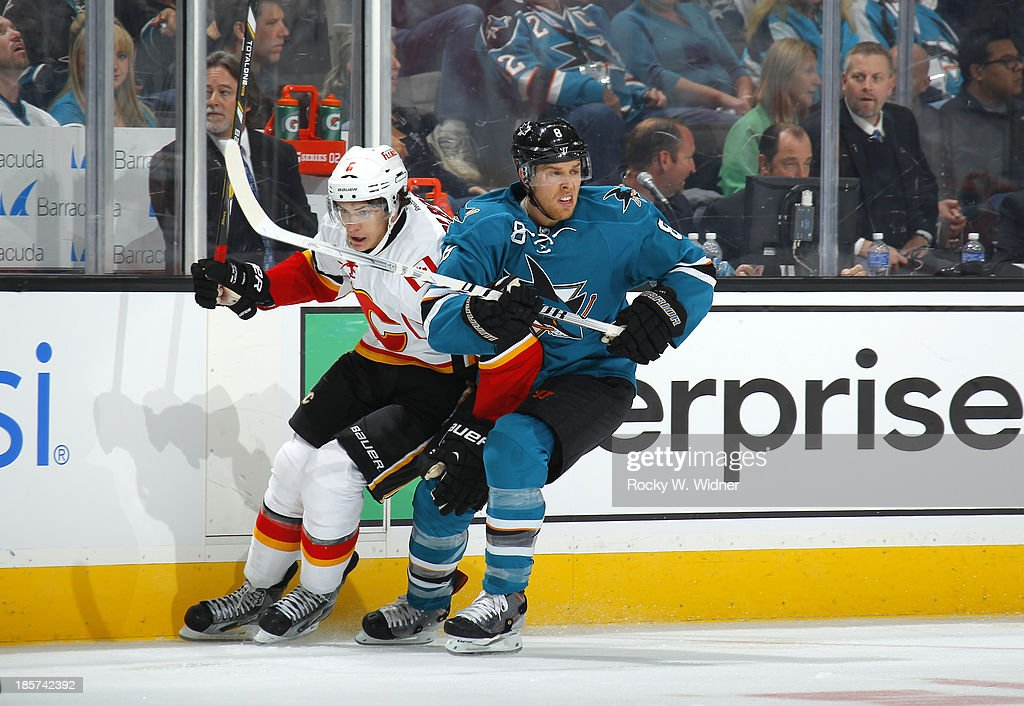 Joe Pavelski #8 of the San Jose Sharks skates against Dennis Wideman #6 of the Calgary Flames at SAP Center on October 19 2013 in San Jose, California.