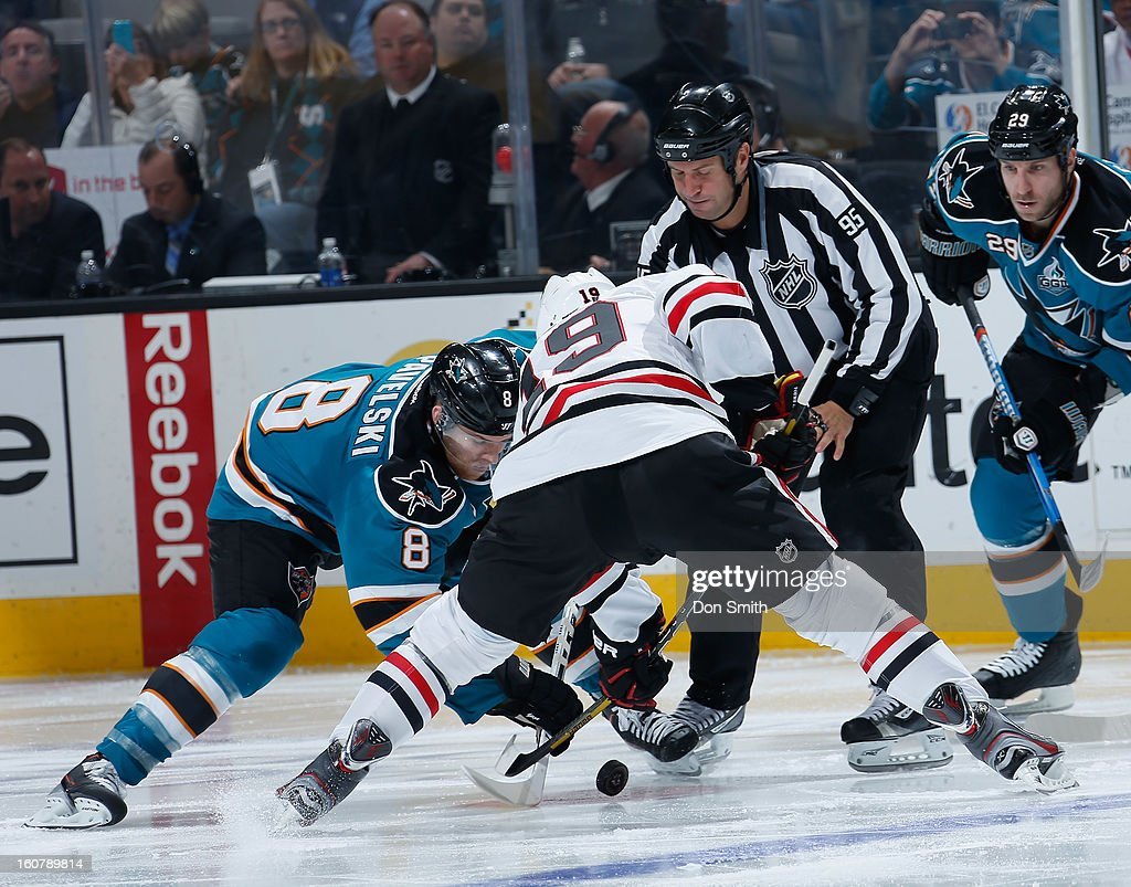 Joe Pavelski #8 of the San Jose Sharks takes a faceoff against Jonathan Toews #19 of the Chicago Blackhawks during an NHL game on February 5, 2013 at HP Pavilion in San Jose, California.