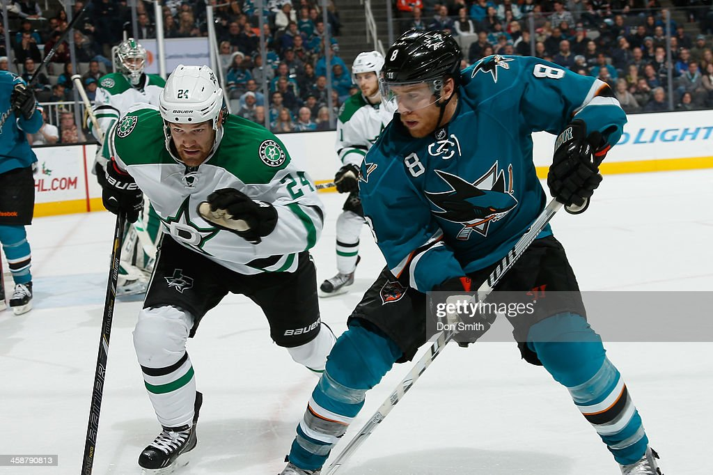Joe Pavelski #8 of the San Jose Sharks tries to get a puck down the ice against Jordie Benn #24 of the Dallas Stars during an NHL game on December 21, 2013 at SAP Center in San Jose, California.