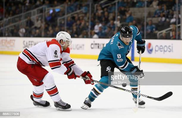 Joe Pavelski of the San Jose Sharks tries to keep puck away from Klas Dahlbeck of the Carolina Hurricanes at SAP Center on December 7 2017 in San...