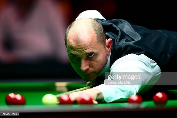 Joe Perry of England plays a shot in his first round match against Barry Hawkins of England during Day Two of the Dafabet Masters at Alexandra Palace...