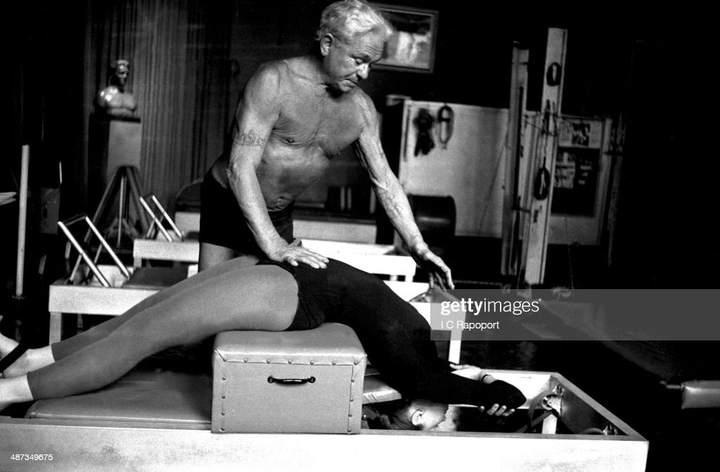 Joe Pilates, Inventor, physical fitness guru and founder of the Pilates exercise method instructs a client on the Short Box and works her through an exercise routine in his 8th Avenue studio on October 4, 1961 in New York City, New York.