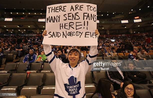 Joe Poon shows off his sign as Toronto Maple Leaf fans watch the Leafs play the Ottawa Senators in Ottawa on the scoreboard at the Air Canada Centre...