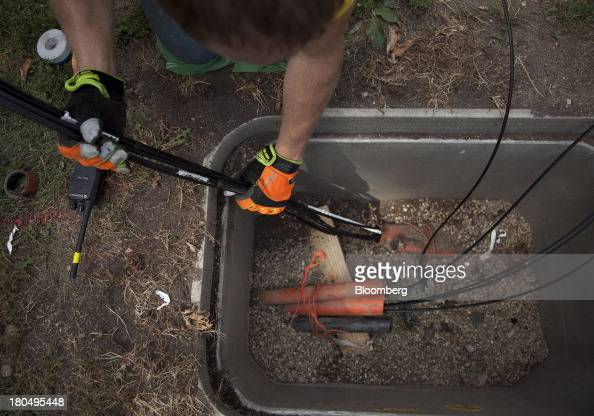 Joe Prehall a master electrician with US Internet Corp feeds fiber optic cables into tubes in the ground during installation in Minneapolis Minnesota...
