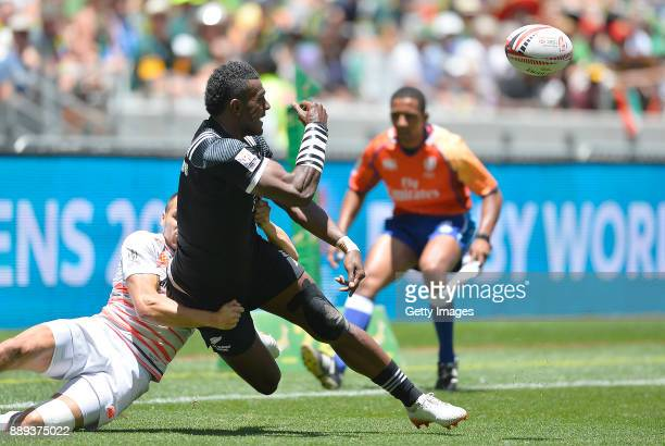 Joe Ravouvou of New Zealand offloads during day 2 of the 2017 HSBC Cape Town Sevens match between England and New Zealand at Cape Town Stadium on...