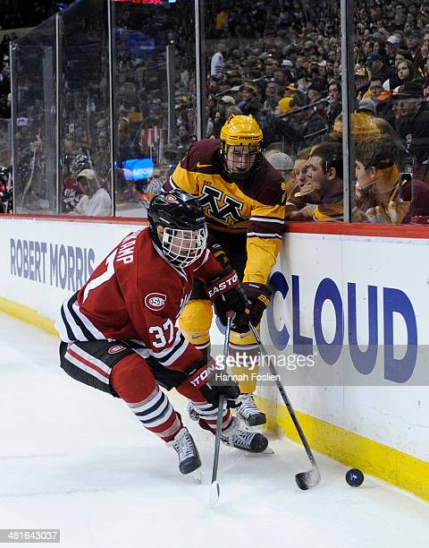 Joe Rehkamp of the St Cloud State Huskies and Brady Skjei of the Minnesota Golden Gophers skate after the puck along the boards during the first...