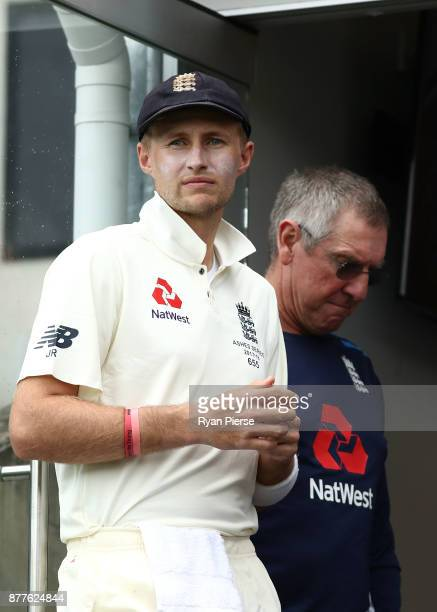 Joe Root of England and England Head Coach Trevor Bayliss look on during a rain delay during day one of the First Test Match of the 2017/18 Ashes...