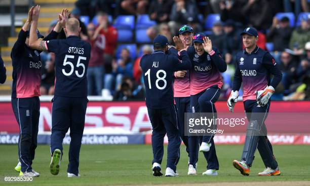 Joe Root of England celebrates with teammates after catching out Martin Guptill of New Zealand during the ICC Champions Trophy match between England...