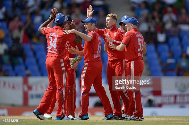 Joe Root of England celebrates with teammates after dismissing Kieran Powell of the West Indies during the 1st One Day International between West...
