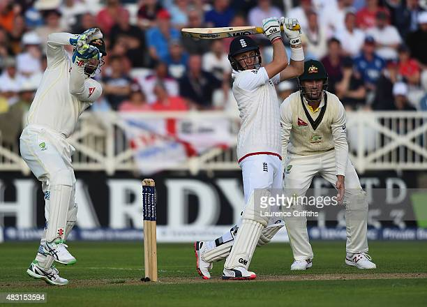 Joe Root of England hits out to the boundary as Peter Nevill of Australia looks on during day one of the 4th Investec Ashes Test match between...