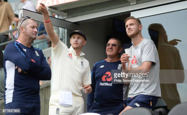 Joe Root of England points at the sky as Trevor Bayliss and Stuart Broad look on during the first Ashes cricket test match between Australia and...