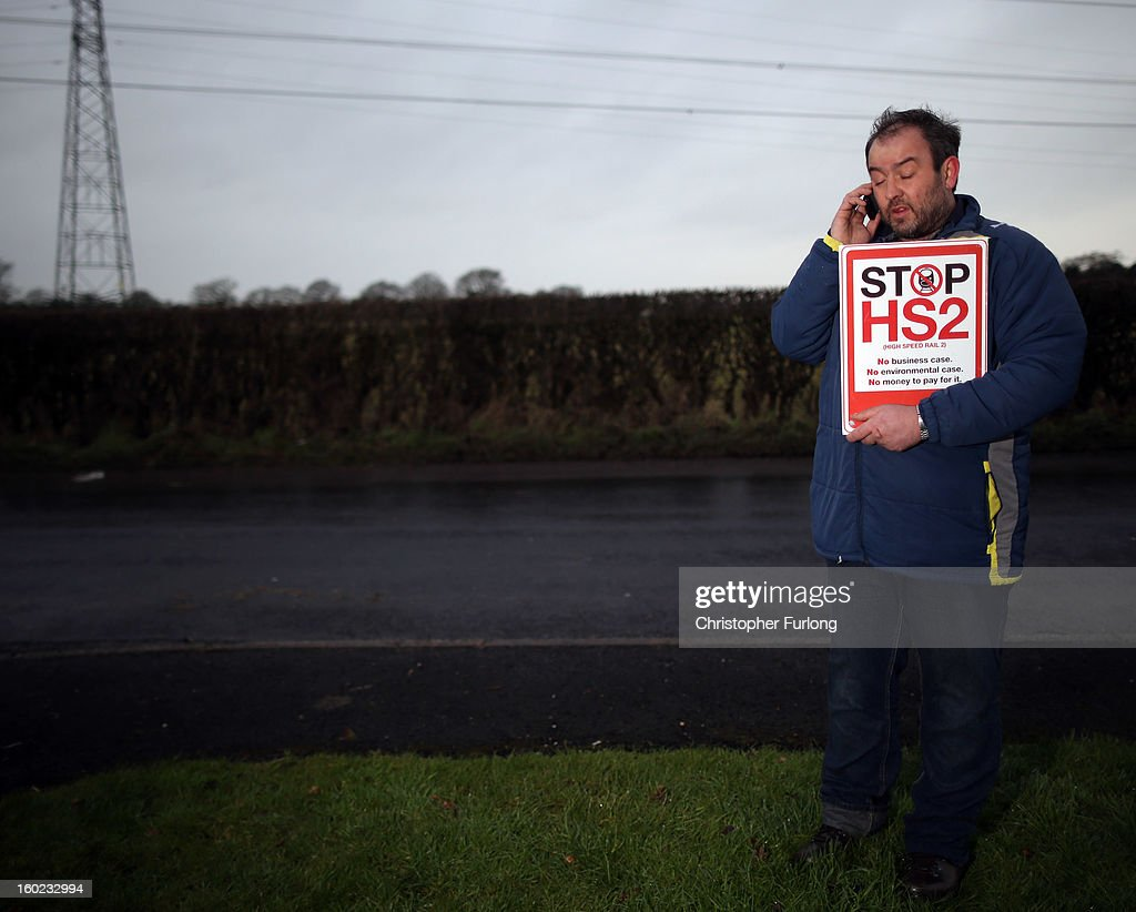 Joe Rukin from the Stop the HS2 Campaign talks on a mobile phone near to the planned location of the new HS2 high speed rail link as it passes by the village of Hoo Green on January 28, 2013 in Knutsford, United Kingdom. The government has today released details of the next phase of the GBP 32 billion HS2 high-speed rail network, which will link Manchester and Leeds.
