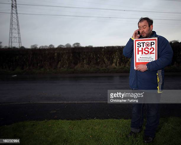 Joe Rukin from the Stop the HS2 Campaign talks on a mobile phone near to the planned location of the new HS2 high speed rail link as it passes by the...
