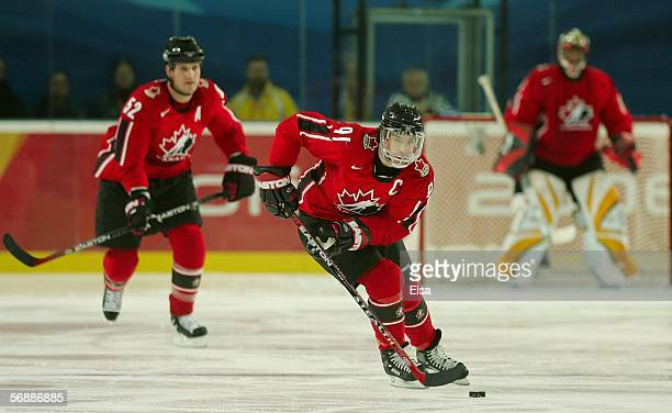 Joe Sakic of Canada brings the puck up the ice in front of teammate Adam Foote during their men's ice hockey Preliminary Round Group A match against...