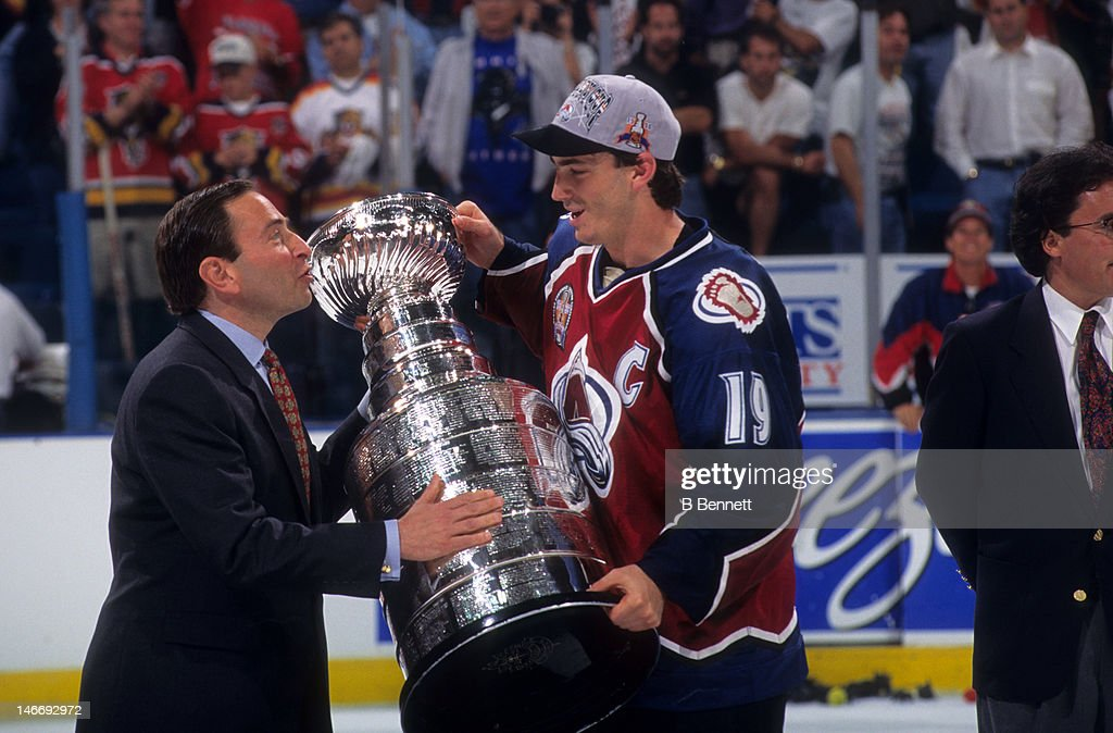 <a gi-track='captionPersonalityLinkClicked' href=/galleries/search?phrase=Joe+Sakic&family=editorial&specificpeople=202869 ng-click='$event.stopPropagation()'>Joe Sakic</a> #19 of the Colorado Avalanche takes the Stanley Cup from NHL commissioner <a gi-track='captionPersonalityLinkClicked' href=/galleries/search?phrase=Gary+Bettman&family=editorial&specificpeople=215089 ng-click='$event.stopPropagation()'>Gary Bettman</a> after the Avalanche defeated the Florida Panthers in Game 4 of the 1996 Stanley Cup Finals on June 10, 1996 at the Miami Arena in Miami, Florida.