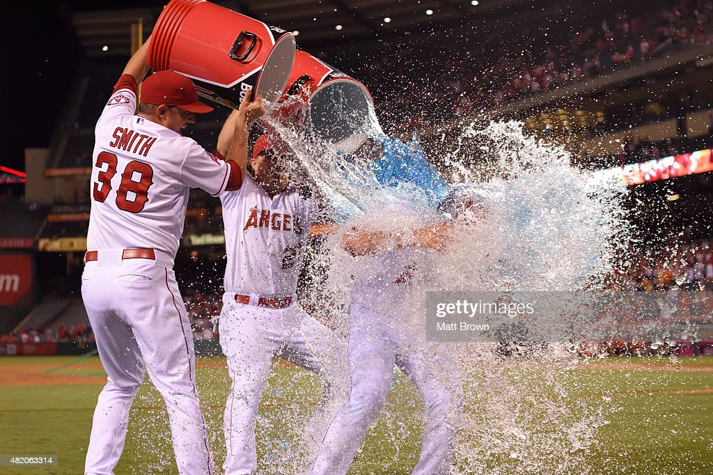 Joe Smith and Mike Trout of the Los Angeles Angels of Anaheim and dump water and Body Armor on Huston Street while celebrating after Street threw his...