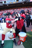 Joe Staley of the San Francisco 49ers shakes hands with 'Bat Kid' Miles Scott on the sideline during the game against the Seattle Seahawks at...